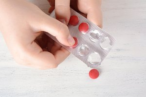 Female hand holding a pill.