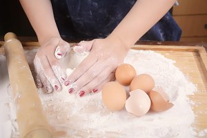 Woman hands knead dough.