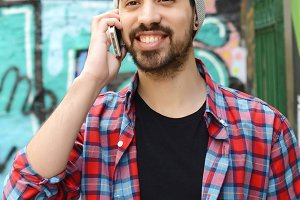 Young latin man talking on the phone