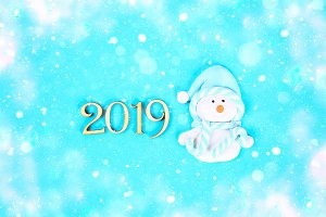 Text 2019 year. Snowman on a blue ba