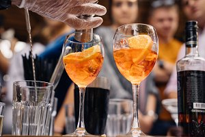 hands of barman who poured aperol