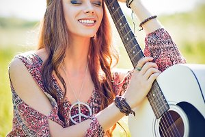 Smiling hippie woman with guitar