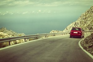 Red car on highway in mountains