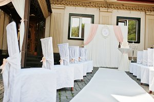 Wedding chairs with pink bows on sit
