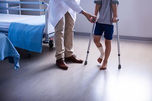 Doctor assisting injured boy to walk
