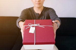Young man giving a red box of gift