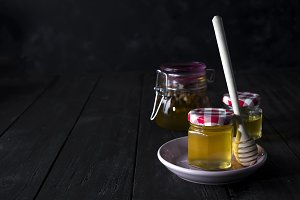 glass jar of honey and stick on a