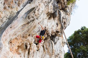 Young man rock climbing on white mou