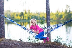 Little girl child in hammock near th