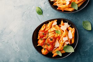 Tasty tomato pasta in bowls on blue