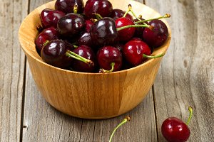 Ripe cherries in bowl on rustic wood