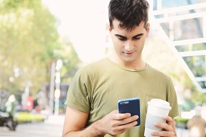 Young man typing message with mobile