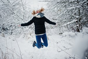 Blonde girl having fun with snow at