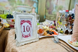 Frame with number ten at table of gu