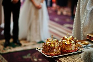 Golden wedding crowns at table on ch