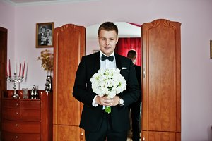 Stylish groom with wedding bouquet a