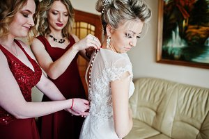 Bridesmaids helped wear bride dress