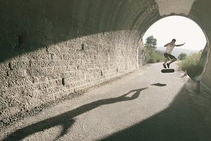 Young man in tunnel with skateboard