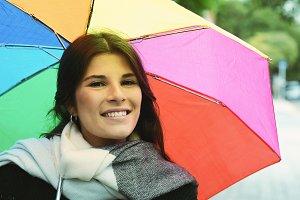 Beautiful woman under rainbow umbrel