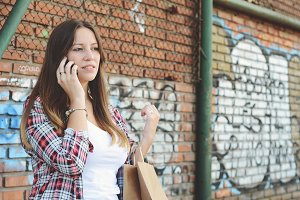 Young woman with shopping bags using