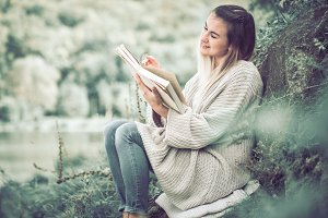 girl in sweaters reading book