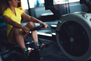 Rowing in the gym. Young woman train