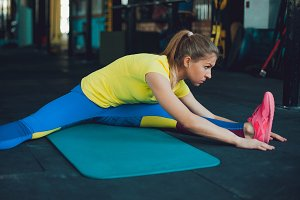 Stretching. Young woman in gym