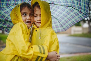 Adorable girls in raincoats hugging