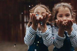 Twin sisters enjoying blowing