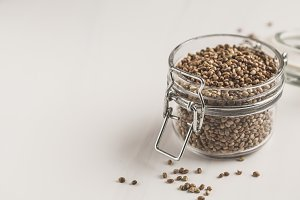 Glass jar of untreated hemp seeds.