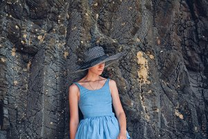 Stylish girl leaning on a stone wall