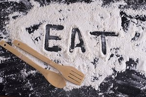 Word eat written in flour with a woo