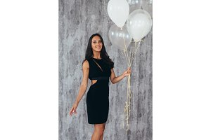 Cheerful young woman with balloons