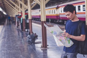 Young man traveler with map on stree