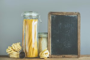 Spaghetti and rice in jars on wooden