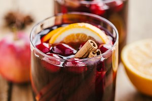 Mulled wine in glass on wooden table