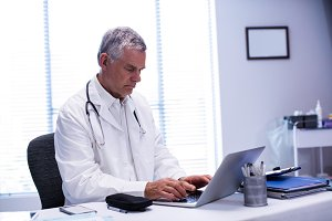 Doctor sitting at table with laptop