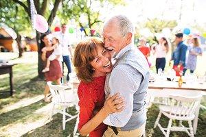 A senior couple dancing on a garden