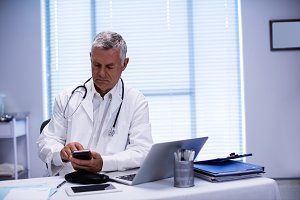 Doctor sitting at table with phone