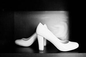 White wedding shoes of bride at wood