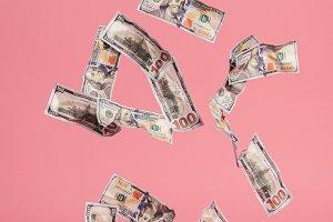 Dollar bills falling down on pink ba