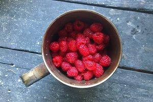 Ripe raspberries in a tin mug on a