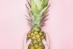 Girl holding ripe pineapple in hands