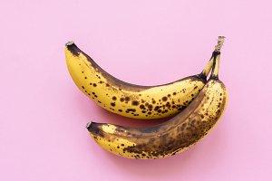 Overripe bananas on pink background