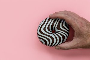 Hand holding striped chocolate donut