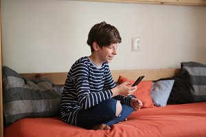 Boy teen with phone on sofa at home
