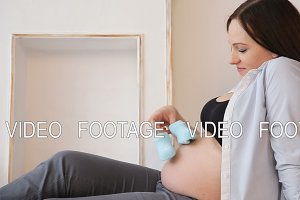 Pregnant woman holding baby shoes on