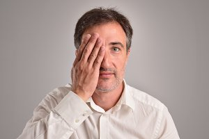 Man covering eye for revision