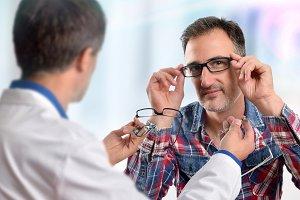 Man choosing eyeglasses in a shop