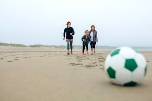 Soccer ball with three running peopl